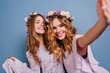 canvas print picture - Ecstatic blonde lady with white flowers in hair taking picture of herself. Indoor portrait of two girls making selfie on bright blue background.