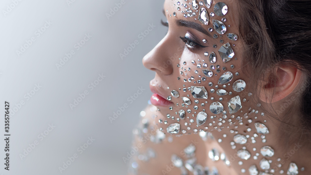 Fototapeta Fantastic fashion portrait of a young beautiful woman with transparent crystals on her face and shoulders.
