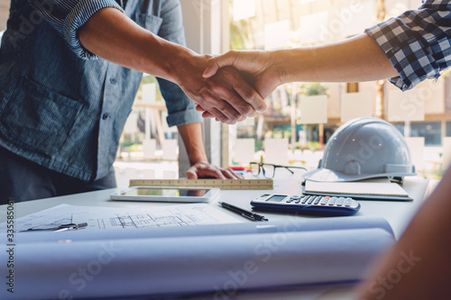 Obraz Architect and engineer construction workers shaking hands while working for teamwork and cooperation concept after finish an agreement in the office construction site, success collaboration concept. - fototapety do salonu