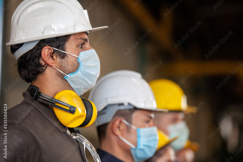 Fototapeta Workers wear protective face masks for safety in machine industrial factory.