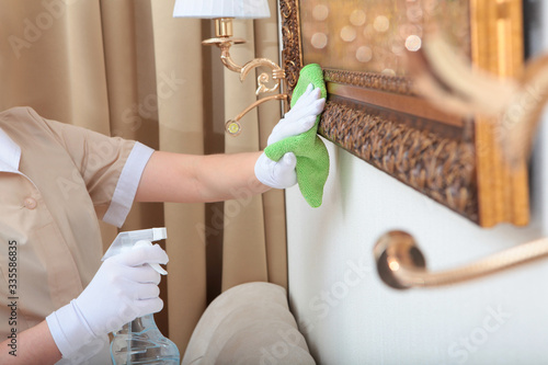 Fototapeta Cleaning agent in the hands of a maid. Hands in white gloves. Spray in a bottle. Cleanliness in the hotel room.Unrecognizable photo.Copy of the space. obraz