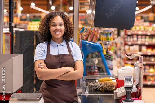 Foto Pretty young smiling African-american female sales clerk looking at you