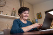 A senior woman with black short hair sits at a desk and works on a laptop computer. She is looking for some new cooking recipes online and She is thoughtful and laughing.