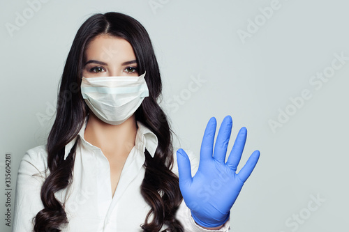 Obraz na płótnie Young woman in medical face mask showing stop pandemic gesture