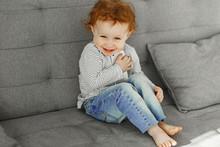 A Little Girl In A Striped Swe...