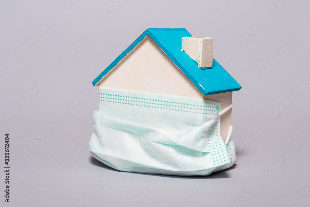 Fototapeta Wooden house in a protective mask, home protection