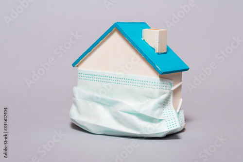 Obraz Wooden house in a protective mask, home protection - fototapety do salonu