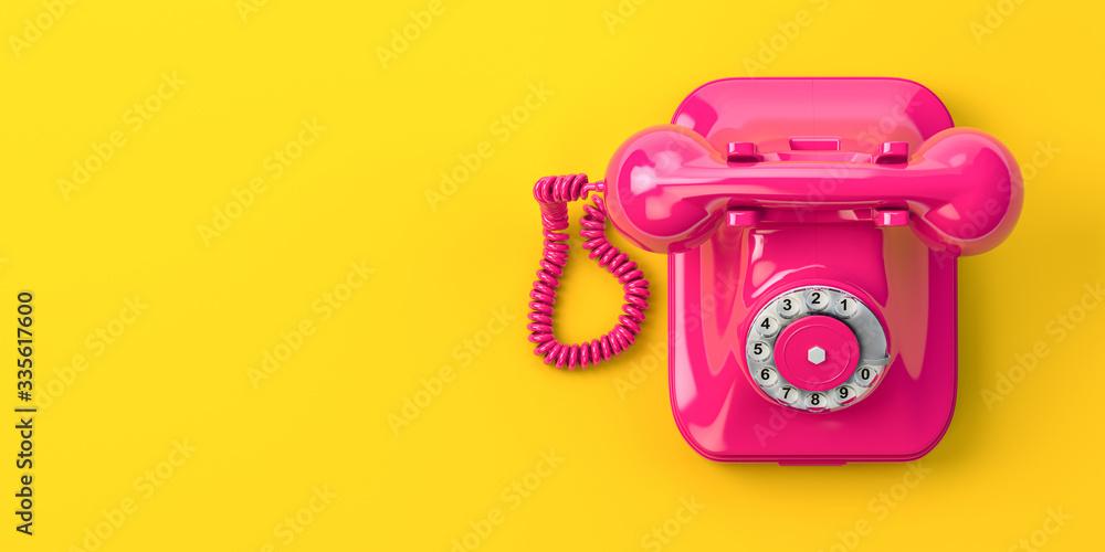 Fototapeta Vintage pink telephone on yellow background.