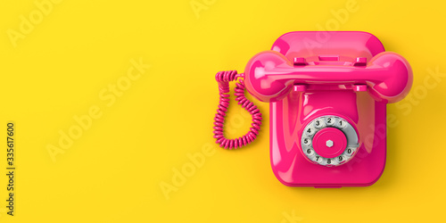 Fototapeta Vintage pink telephone on yellow background. obraz