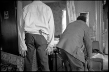 Two Men Tussling In Living Room