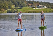 Two Females Riding A Stand Up Paddle Board In The Smartinsko Lake In Slovenia