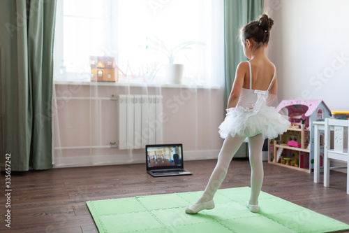 Fényképezés Pretty young ballerina practicing classic choreography during online class in ba