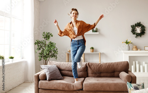 Fototapeta Cheerful woman listening to music and dancing on soft couch at home in day off. obraz