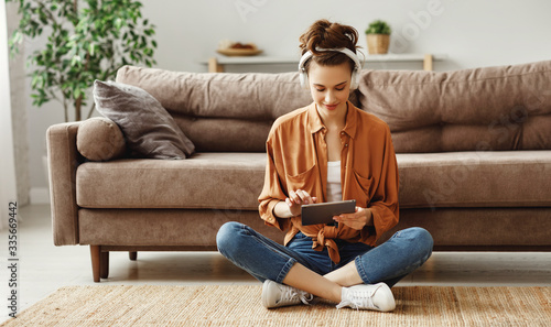 Happy pensive woman using digital tablet at home.