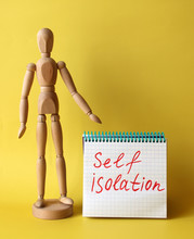 Two Wooden Figures Stand Next To The Notepad With Sign Self Isolation. Concept Of Quarantine Or Self-isolation Due To The Pandemic Of Coronavirus Covid-19