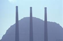 Three Smoke Stacks At A Utility Plant In Morro Bay, California