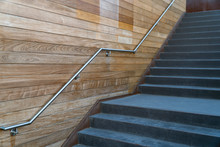 A Metal Stair Handle Attached To The Wooden Wall. Concrete Stairs