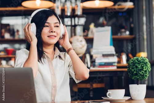 Fototapeta Lifestyle freelance woman he using earphones listening music during working on laptop computer obraz na płótnie