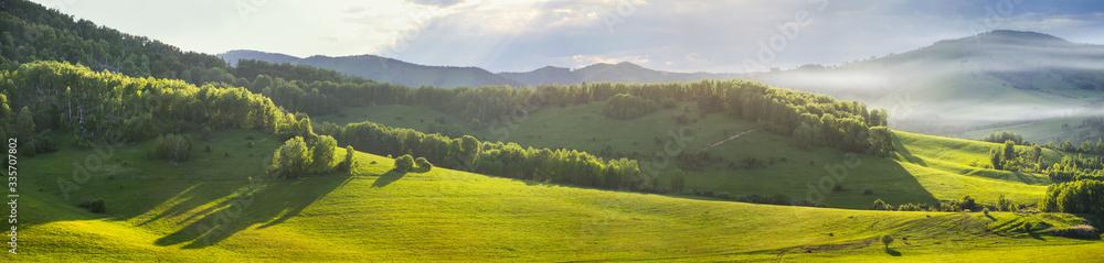 Fototapeta Panoramic mountain views, green hills and meadows. Morning light, fog.
