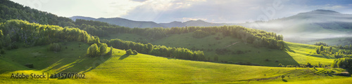 Panoramic mountain views, green hills and meadows. Morning light, fog. - 335707802