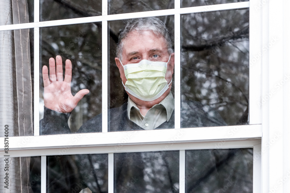 Fototapeta Man wearing mask with his hand up waving at the window