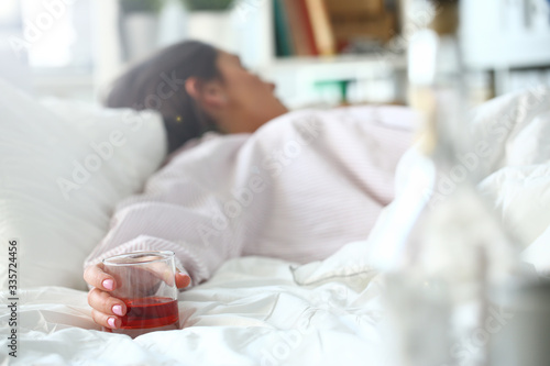 Obraz na plátne Young woman lying in bed deadly drunken holding near-empty bottle of booze