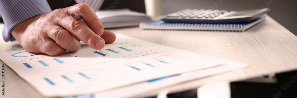 Fototapeta Accountant Calculate Tax Invoice Using Calculator. Man Writing Note about Asset Cost at Office. Paycheck Accounting with Colorful Chart. Audit and Calculating Expense Annual Financial Report
