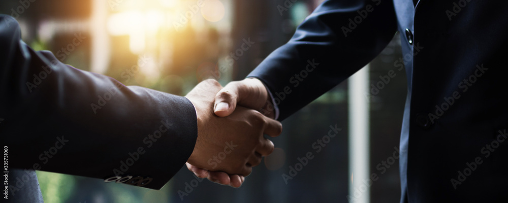 Fototapeta successful negotiate and handshake concept, two businessman shake hand with partner to celebration partnership and teamwork, business deal