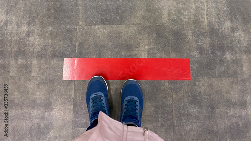 Foto Person standing on tiled floor with a red line