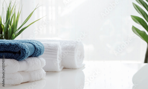 Stampa su Tela Clean towels and houseplant on white table.
