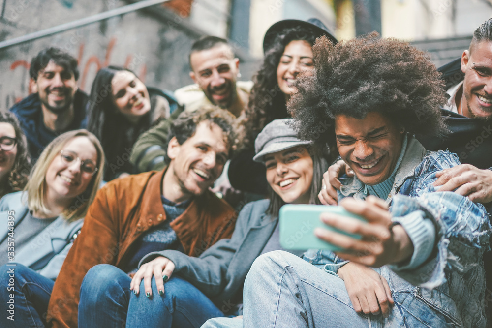 Fototapeta Happy multiracial friends taking selfie and recording videos - Youth and friendship concept  - Main focus on afro man face