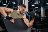 Muscular man building biceps with dumbbell.