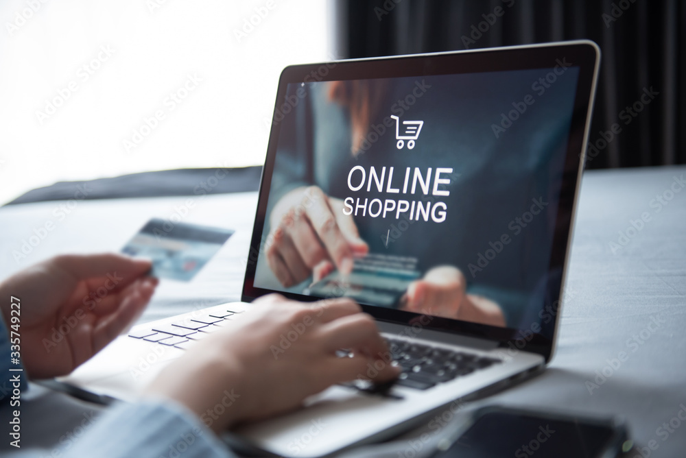 Fototapeta E-commerce and online shopping concept, Woman hand using laptop (Mockup website) and holding credit card for shopping payment online at home.