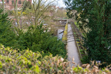 03.04.2020: Garden Landscape: Winding Footpath In An Old Park Among Green Trees Passes Over The Openwork Pedestrian Bridge . Park Schoenbusch - English Landscape Garden, Aschaffenburg, Germany