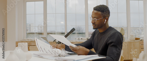 Obraz na płótnie Handsome African American male working from home, using laptop in living room, c