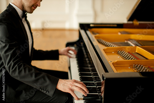 Fototapeta professional caucasian pianist practicing before concert on a stage
