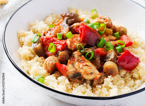 Obraz na plátně Bulgur and sauteed chicken, mushrooms, eggplants, paprika and tomatoes in a white bowl