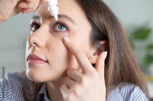 Fotomural Closeup view of young woman applying eye drop