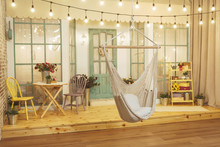 Suspended Wicker Swing On The Summer Porch With Garlands Of Light Bulbs. Swing Hammock Made Of Thread On The Background Of The House Verandah. Terrace Of The Summer House Design Of The Photo Studio.