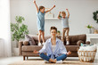 canvas print picture - Happy mother with closed eyes meditating in lotus pose on floor trying to save inner harmony while excited children jumping on sofa and screaming in light spacious living room.