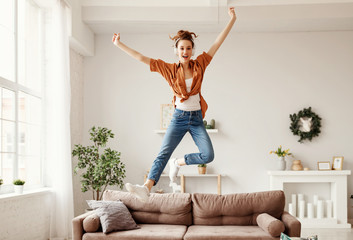Excited millennial woman listening to music and having fum at home