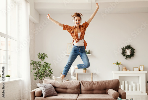 Fotografia Excited millennial woman listening to music and having fum at home