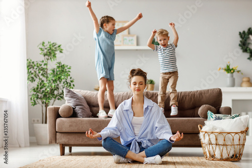 Happy mother with closed eyes meditating in lotus pose on floor trying to save inner harmony while excited children jumping on sofa and screaming in light spacious living room Canvas