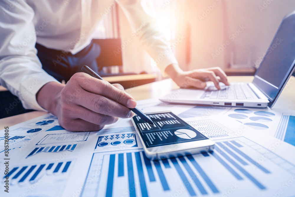 Fototapeta Businessman accountant or financial expert analyze business report graph and finance chart at corporate office. Concept of finance economy, banking business and stock market research.