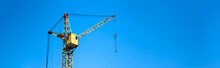 Yellow Construction Elevator Crane Close-up Against The Blue Sky, Panoramic Mock-up With Space For Text