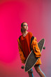canvas print picture - A young girl with bright makeup holds a longboard in her hands on a fashionable neon color background. Portrait of a girl skater
