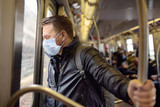 Fototapeta Nowy Jork - Mature man wearing disposable medical face mask in car of the subway in New York during coronavirus outbreak.
