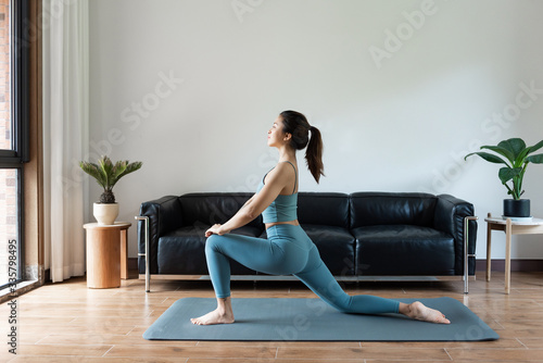 Photo A young Asian woman doing yoga at home