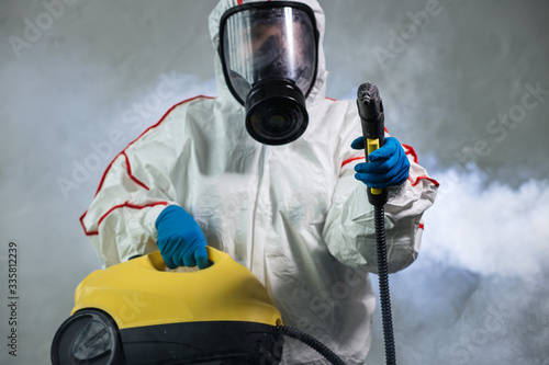 Fotografía professional disinfector in protective suit holding chemical sprayer and other equipment for sterilization and decontamination of viruses, infectious diseases
