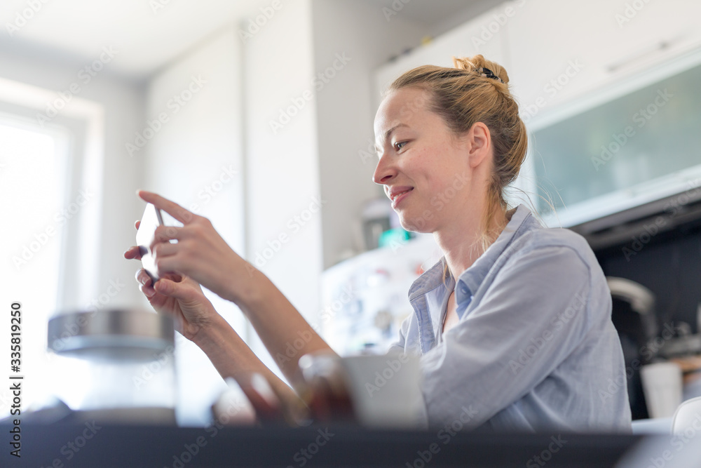 Fototapeta Young smiling cheerful woman indoors at home kitchen using social media on phone for video chatting and stying connected with her loved ones. Stay at home, social distancing lifestyle.